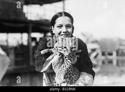 Porträt einer jungen Frau trägt eine Gepard Cub und lächelnd - Stockfoto