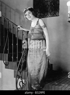 Junge Frau eine Treppe hinunter bewegt und lächelnd - Stockfoto