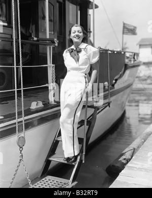 Porträt einer jungen Frau auf Schritte eines Bootes stehen und Lächeln - Stockfoto