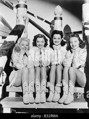 Porträt von vier jungen Frauen sitzen auf Stufen in westlicher Kleidung - Stockfoto