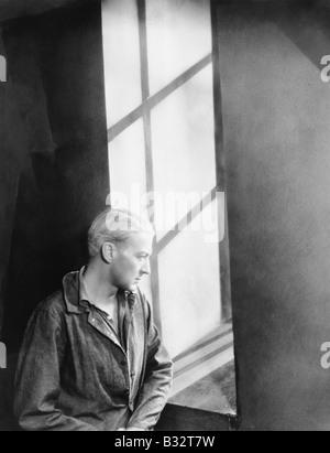Junger Mann, Blick durch ein Fenster - Stockfoto