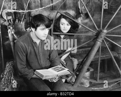 Junger Mann liest ein Buch und eine junge Frau neben ihm zu sitzen - Stockfoto