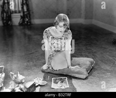 Frau kniend auf einem Kissen mit Blick auf ein zerrissenes Bild eines Mannes - Stockfoto