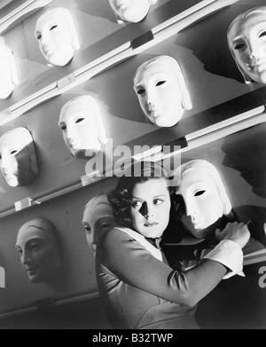 Frau, die Angst hielt sich an eine Maske an der Wand der Masken - Stockfoto