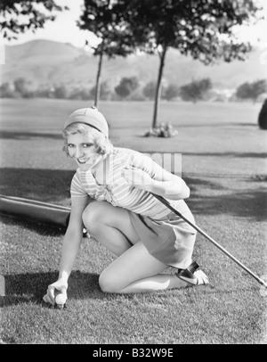 Junge Frau auf einem Golfplatz Platzierung einen Golfball - Stockfoto