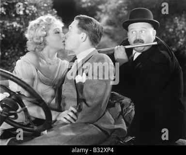 Junges Paar küssen einander liebevoll, während ein Mann spielt Querflöte - Stockfoto