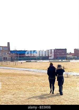 Zwei Frauen gehen durch ein Feld in Richtung einer städtischen Nachbarschaft - Stockfoto
