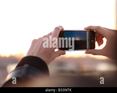 Eine junge Chinesin nutzt ihr Handy, um ein Foto aufzunehmen. - Stockfoto