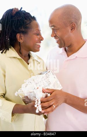 Mann und Frau hält lächelnd Geschenk - Stockfoto