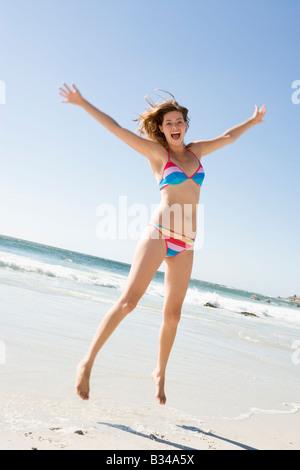 Frau in einem zweiteiligen Badeanzug springen auf einem Strand - Stockfoto