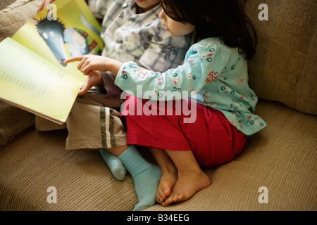 Jungen im Alter von sechs Jahren liest eine Geschichte um seine kleine Schwester im Alter von fünf Jahren