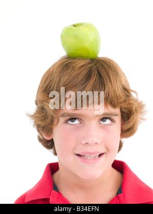 Junge mit Apple auf seinen Kopf lächelnd - Stockfoto