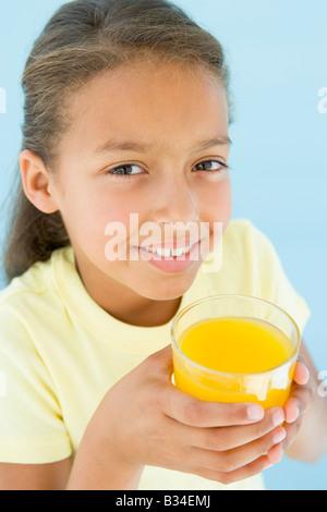 Junges Mädchen mit Glas Orangensaft lächelnd - Stockfoto