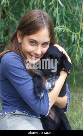 junge Teenager-Mädchen Kuscheln ein Labrador-Welpe - Stockfoto
