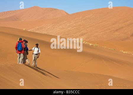 Besucher wandern unter den Dünen im Sossusvlei Namibia Afrika - Stockfoto
