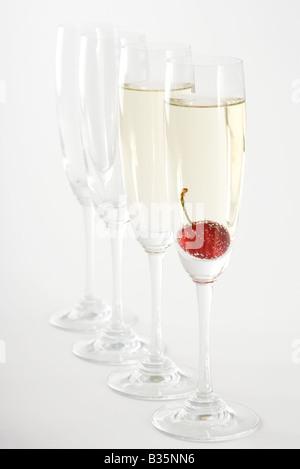 Sektgläser, zwei gefüllt mit Champagner, einem mit einer Kirsche im Wasser - Stockfoto