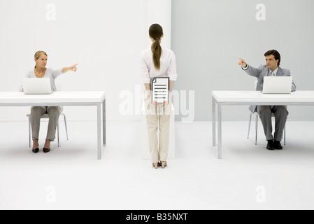Mitarbeiter im Büro am Schreibtisch sitzen, zeigen beide Frau Holding Dokument hinter ihrem Rücken - Stockfoto