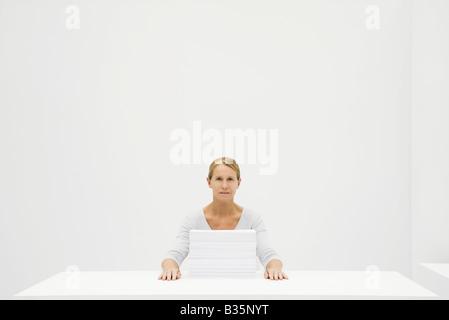 Weibliche Büroangestellte sitzen hinter Papierstapel, Blick in die Kamera - Stockfoto