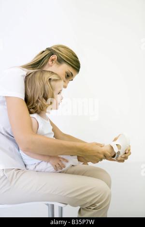 Mutter hilft ihrer kleinen Tochter ihrem Schuh anziehen, Mädchen sitzt auf dem Schoß - Stockfoto
