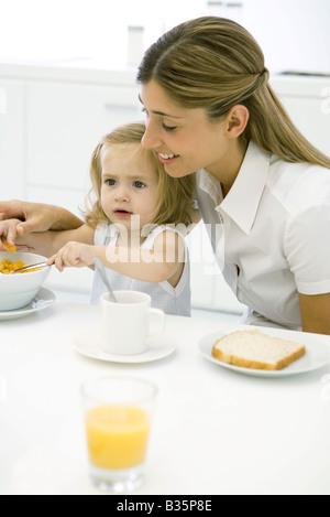 Mutter und Tochter sitzen am Tisch, Essen Frühstück - Stockfoto