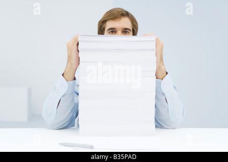 Mann über hohe Stapel von Papier - Stockfoto