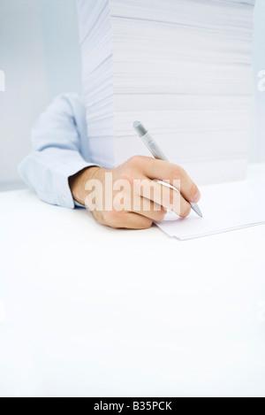 Arm zu erreichen um massive Papierstapel auf ein einzelnes Blatt zu schreiben - Stockfoto