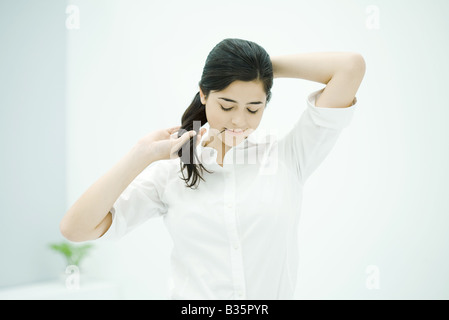 Frau Haar befestigen, Haarnadel im Mund halten, nach unten - Stockfoto