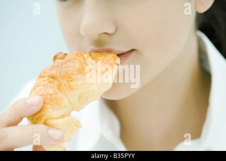 Junge Frau Essen Croissant, close-up, beschnitten Ansicht - Stockfoto