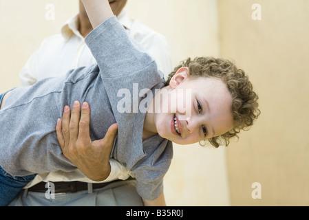 Junge, die vorgibt, ein Flugzeug, von seinem Vater gehalten werden - Stockfoto