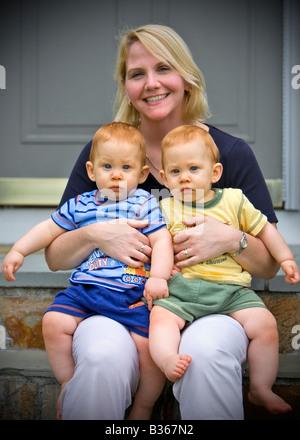 Blonde hübsche Mutter hält süße Twin Baby boys - Stockfoto