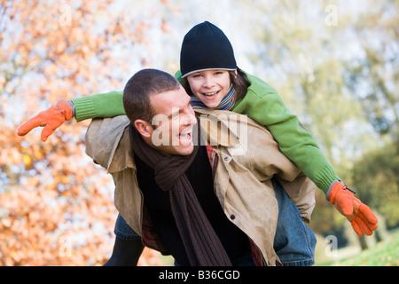 Vater im freien Sohn huckepack und lächelnd (Tiefenschärfe) - Stockfoto