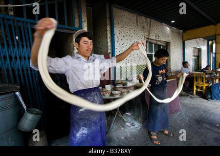 Uyghur Mann machen frische Laghman Nudeln auf dem Sonntagsmarkt in Kashgar in der Provinz Xinjiang in China - Stockfoto