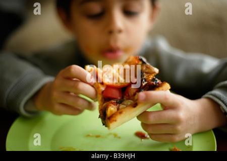 Hausgemachte Pizza sechs Jahre alter Junge steckt in eine Scheibe von seiner Mutter s Hausmannskost Mischlinge indischen - Stockfoto