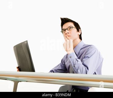 Asiatische Geschäftsmann am Schreibtisch arbeiten am Laptop denken - Stockfoto