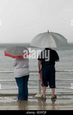 2 Personen im Sommer Urlaub Urlaub stehen im Regen unter Sonnenschirmen an Aberystwyth Strandpromenade August 2008 - Stockfoto