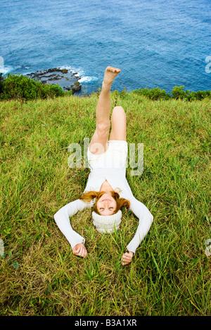 Fröhliche junge Frau entspannende Gras in der Nähe von Meer in Maui Hawaii - Stockfoto