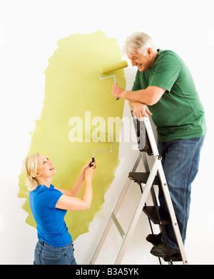 Applying paar Malerei Wand grün mit männlich auf Leiter - Stockfoto