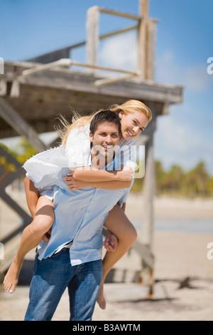 Hispanic Mann geben Huckepack-Fahrt, Freundin - Stockfoto