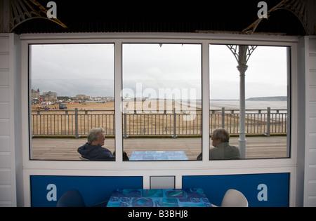 Zwei Rentner Schutz vor dem Wind auf der Grand Pier, Weston-Super-Mare, England. - Stockfoto