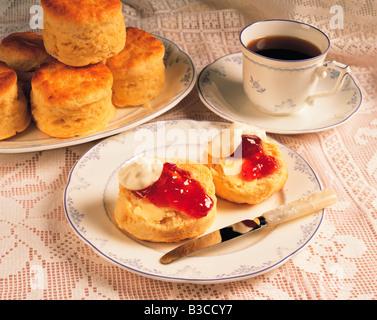 Tasse Kaffee mit Gebäck, Sahne und Marmelade. - Stockfoto