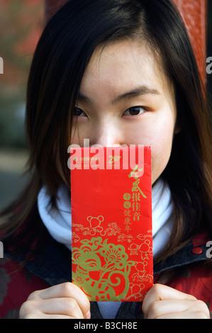 China, Peking. Ein chinesisches Mädchen, traditionellen chinesischen Stil Kleidung hält eine Hongbao Briefumschlag, - Stockfoto