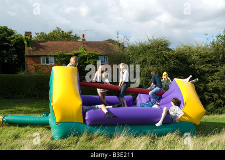 Jugendliche auf aufblasbare Hüpfburg outdoor Party Spielen - Stockfoto