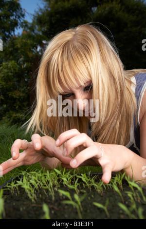 junge blonde behaarte Frau späten Teenager Anfang zwanzig Gesten wütend auf ein Tablett mit Petersilie Kraut Sämlinge - Stockfoto