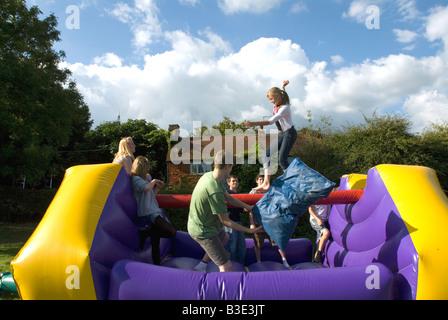 Jugendliche spielen auf eine aufblasbare Hüpfburg Outdoor-Geburtstags-party - Stockfoto