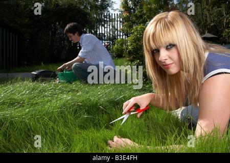 junger Mann Frau blonde kurzhaarige Frau dunkelhaarigen Mann paar späten Teenager Anfang zwanzig schneiden mit der - Stockfoto