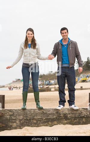 Paar steht auf einem Zaun am Strand - Stockfoto