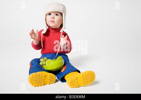 Ein Junge hielt eine Schale mit Trauben - Stockfoto
