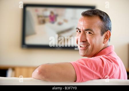 Mann im Wohnzimmer Fernsehen lächelnd beobachten - Stockfoto