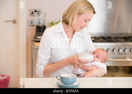 Mutter Fütterung Baby in Küche mit Kaffee - Stockfoto