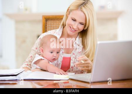 Mutter und Kind im Speisesaal mit Laptop lächelnd - Stockfoto
